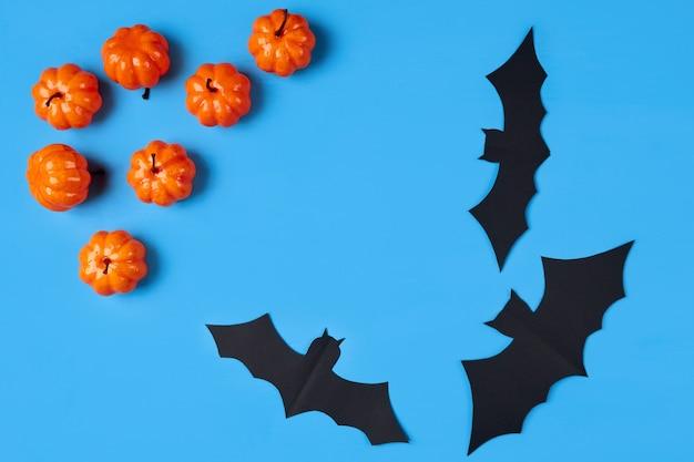 テキストのための場所と青い背景の上のいくつかの装飾的なオレンジ色のカボチャと紙のコウモリ。ハロウィーンの休日のコンセプト。フラットレイアウト、フラットリー