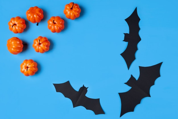 Several decorative orange pumpkins and paper bats on a blue background with place for text. halloween holiday concept. flat layout, flatley