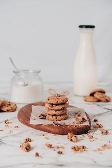 신선한 우유와 설탕 항아리와 흰색 배경에 갓 준비된 초콜릿 부스러기와 여러 맛있는 쿠키