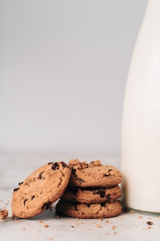 신선한 우유 한 병에 갓 준비된 초콜릿 부스러기와 몇 가지 맛있는 쿠키
