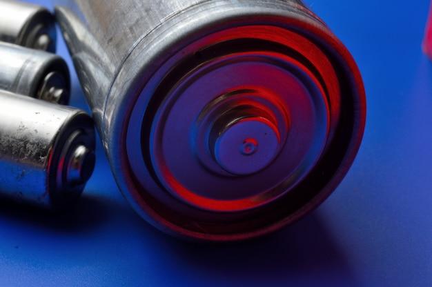 青い背景にいくつかの異なる電池。閉じる。