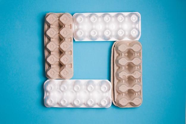 Несколько разных ящиков для яиц на синем фоне, копия пространства, вид сверху