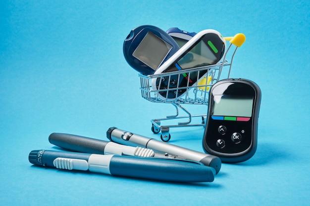 Несколько разных глюкометров в тележке для покупок на синем фоне, ручки для инсулиновых шприцев для пациентов с диабетом, место для копирования, покупка и продажа устройств для диабета