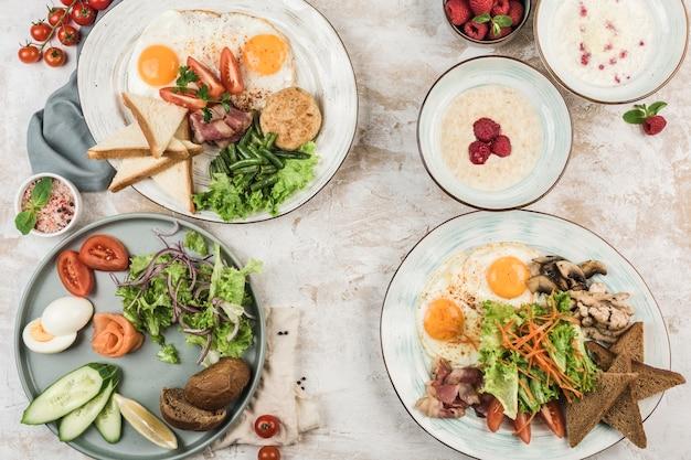 스크램블 에그, 삶은 계란, 쌀 죽, 요리사의 흐름과 함께 접시에 귀리와 함께 여러 요리, copyspace와 평면도. 평평한 평신도. 아침 식사의 개념. 레스토랑 음식.