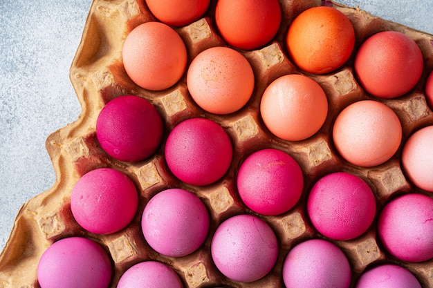 Several easter eggs in different shades of pink in eggbox
