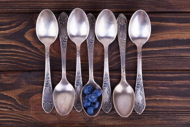 Several empty teaspoons and one spoon with berries