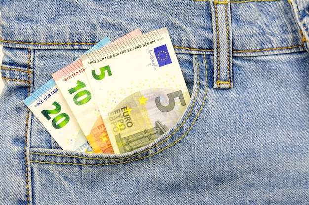 Several euro bills are inserted into the jeans pocket