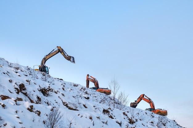 여러 굴착기가 쓰레기 처리장의 거대한 산에서 일합니다.