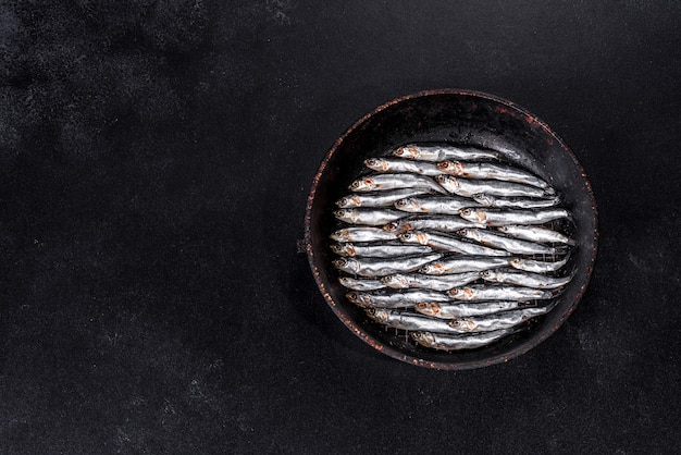 Several fish salted anchovies on a dark concrete table. concept of small fish