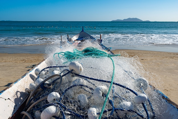 Several fishermen doing artisanal fishing with trawl, on a blue sky day
