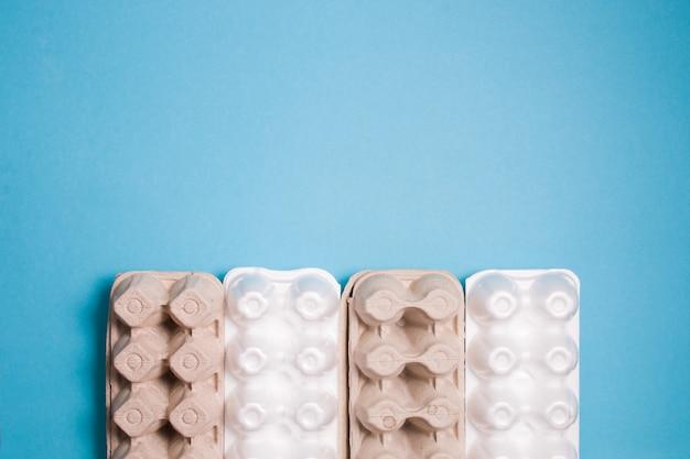 Несколько пенопластовых и картонных упаковок для яиц лежат в ряд на синем фоне, вид сверху, место для копирования, концепция сортировки отходов, экологические материалы против пластика