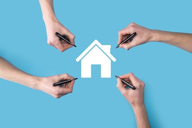 いくつかの、4つの手がマーカーで家のアイコンを描きます。不動産の概念。財産保険とセキュリティの概念。革新技術インターネットネットワークの概念。
