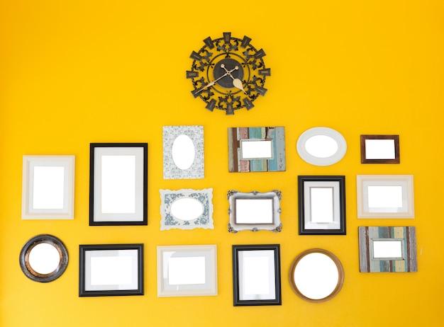 黄色い壁のヴィンテージクロックにいくつかのフレーム