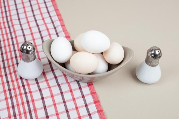 Diverse uova bianche di pollo fresco in lamiera grigia sulla tovaglia.