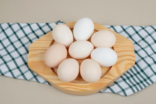 Diverse uova bianche di pollo fresco sul piatto di legno.
