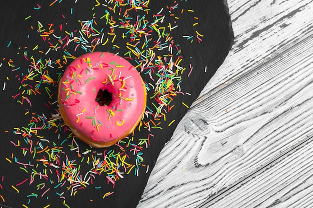 Several fresh donuts in a black ceramic plate on a wooden surface table