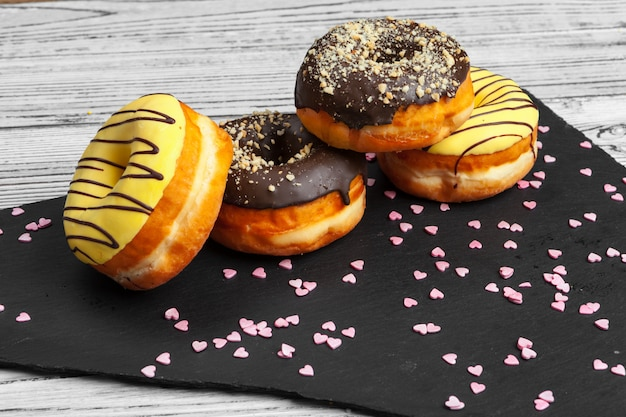 Several fresh donuts in a black ceramic plate on a wooden table