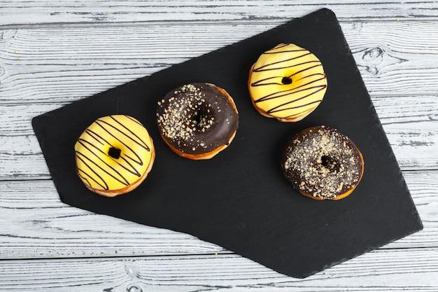 Several fresh donuts in a black ceramic plate