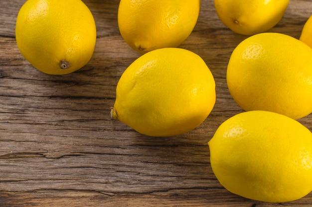 木製の背景にいくつかの新鮮なジューシーなレモン