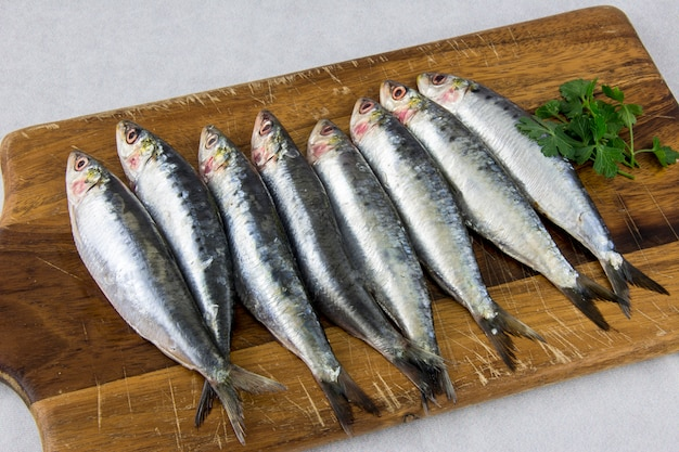 Several fresh sardines on a wooden board