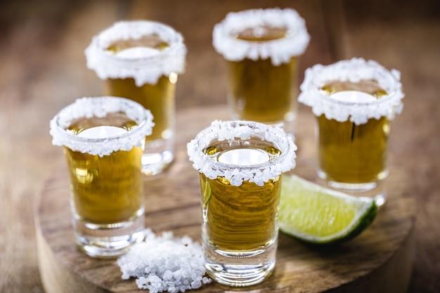 木製のテーブルにレモンと塩とメキシコのゴールドテキーラのいくつかのグラス