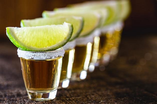 蒸留酒、レモン、塩、青リュウゼツランで作られたメキシコ文化の飲み物であるテキーラのグラスが数杯並んでいました。国際テキーラの日。テキスト用にコピーします。