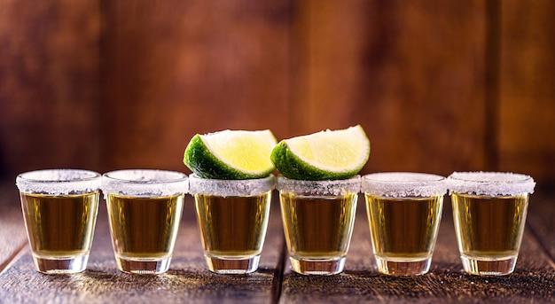 蒸留アルコール、レモン、塩、青いリュウゼツランで作られたテキーラのグラスが数杯並んでいます。メキシコ文化の飲み物です。