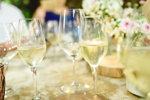 Several glasses with bubbly and fresh champagne served on the table of a banquet.