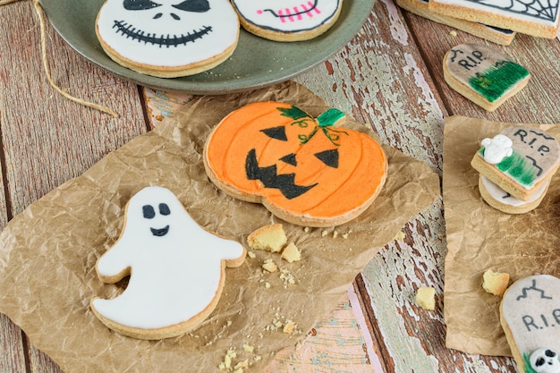 Несколько масляных печений на тему хэллоуина, рядом с крошками и на оберточной бумаге.