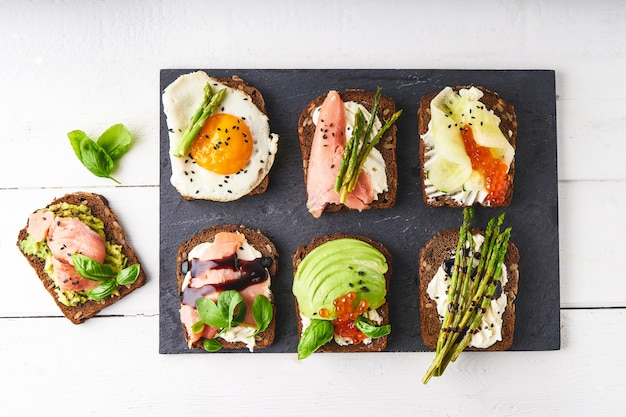 Several healthy sandwiches with different fillings. fish, caviar, avocado, asparagus, cucumber, herbs, sesame seeds, gluten-free bread served on a dark platter