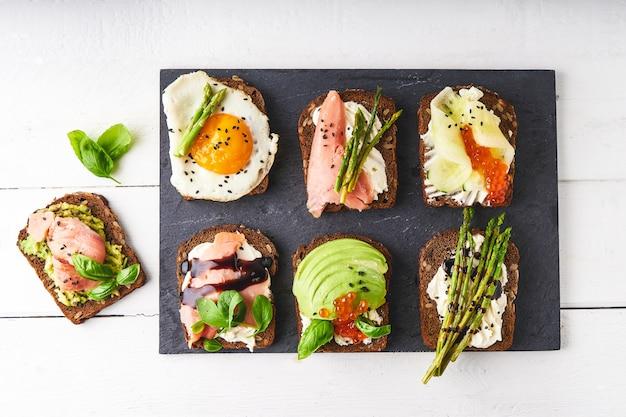 Несколько полезных бутербродов с разной начинкой. рыба, икра, авокадо, спаржа, огурец, зелень, семена кунжута, безглютеновый хлеб на темном блюде