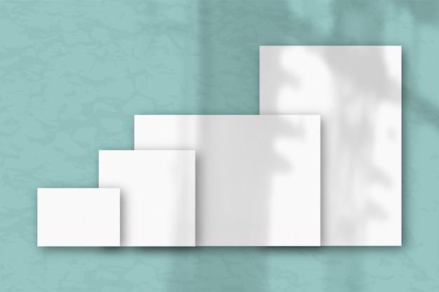 Несколько горизонтальных и вертикальных листов белой текстурированной бумаги на фоне сине-зеленой стены. естественный свет отбрасывает тени из окна. плоская планировка, вид сверху. горизонтальная ориентация
