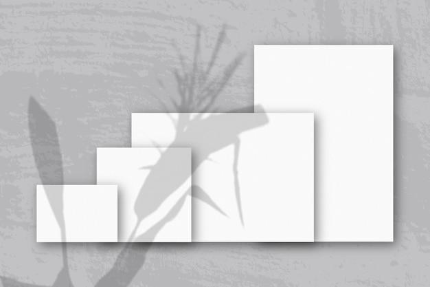 Несколько горизонтальных и вертикальных листов белой текстурированной бумаги на серой стене