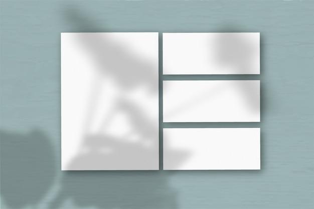 Несколько горизонтальных и вертикальных листов белой фактурной бумаги на фоне сине-зеленой стены. естественный свет отбрасывает тени от герани. плоская планировка, вид сверху. горизонтальная ориентация