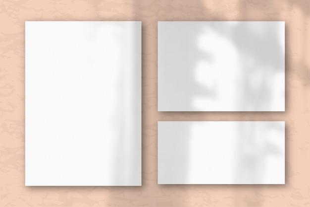 Несколько горизонтальных и вертикальных листов белой фактурной бумаги на фоне розовой стены. естественный свет отбрасывает тени из окна. плоская планировка, вид сверху. горизонтальная ориентация