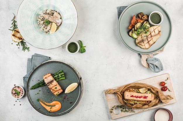 Несколько горячих рыбных блюд, приготовленных на гриле в разных тарелках, которые подаются шеф-поваром на светлом фоне, вид сверху с копией пространства. плоская планировка. ресторанная еда.