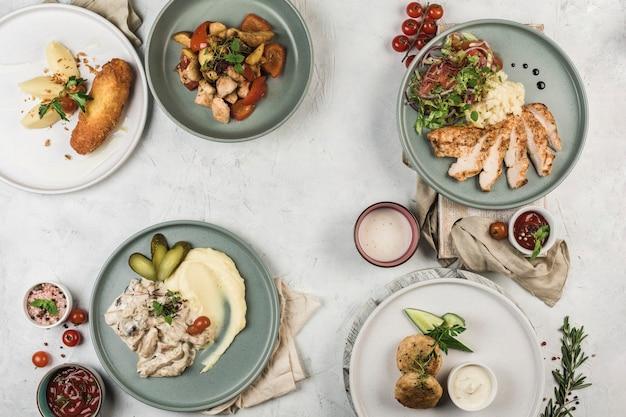 Несколько горячих мясных блюд, приготовленных на гриле в разных тарелках, которые подаются шеф-поваром на светлом фоне, вид сверху с копией пространства. плоская планировка. ресторанная еда.