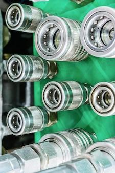 녹색 패널에 여러 유압 커플링 커넥터.