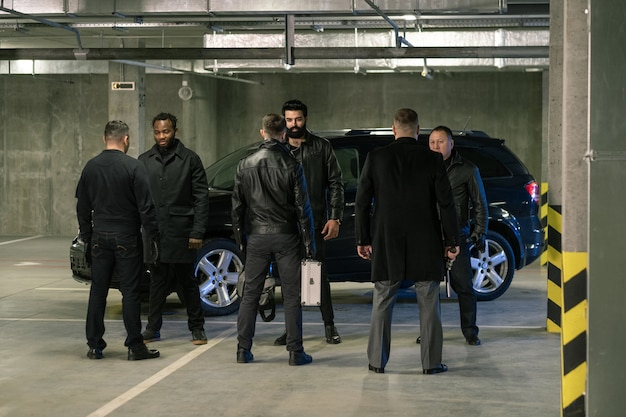 Several intercultural men in black holding handguns and suitcase while discussing terms of criminal business on parking area