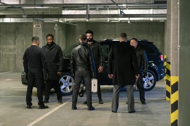 주차 구역에서 범죄 사업 조건을 논의하면서 권총과 가방을 들고있는 검은 색의 여러 이문화 남성