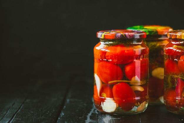 잘 익은 토마토와 마늘을 곁들인 통조림 토마토 몇 병.