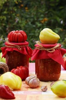 Несколько банок помидоров с перцем и чесноком с размытым фоном растительности