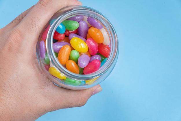 Diversi jelly beans sullo sfondo blu all'interno del vaso di vetro
