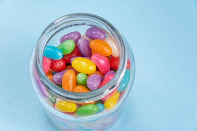 Diversi jelly beans sulla superficie blu all'interno della pentola di vetro