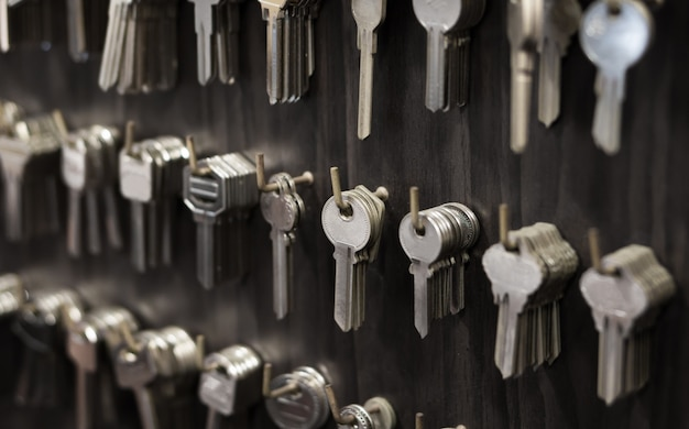 Several keys such as household and car key for copying hang on the wall in the locksmith