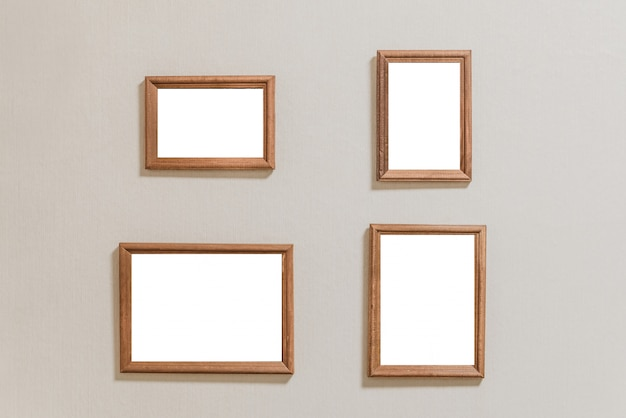 Several a lot of small empty picture frames on a light wall.