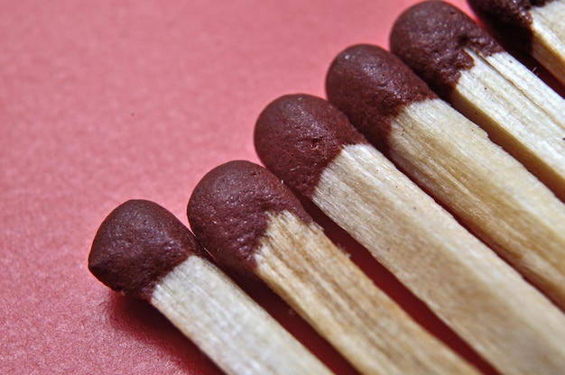 Several matches on a red background. macro shot.