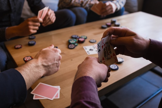 Several men are playing poker in a cafe, holding cards in their hands.