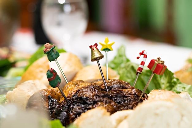 クリスマスディナーのために七面鳥に刺さったクリスマスオブジェクトの先端を持ついくつかの金属箸