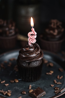 Several muffins or cupcakes with chocolate shaped cream at black table. festive candle burns on a chocolate cake